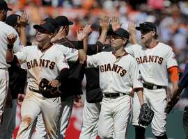 The Giants outfield, Gregor Blanco (left), Nori Aoki and Hunter Pence congratulated teammates after the victory. The San Francisco Giants defeated the Milwaukee Brewers 5-0 to take the series at AT&T Park Wednesday July 29, 2015.