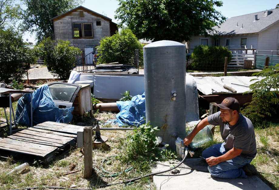 Freddie Beltran Jr.,  a volunteer with the Porterville Area Coordinating Council, prepares in April to install a 300-gallon tank with a pump at the home of  an East Porterville (Tulare County) family  whose  well had  run dry. Photo: Leah Millis / Leah Millis / The Chronicle / ONLINE_YES
