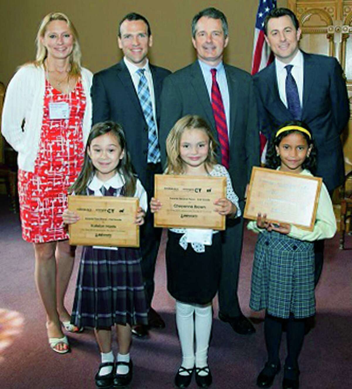 Cheyenne Brown, front middle, who just finished first grade at Northville School in New Milford, recently earned second place in the 11th annual eesmarts student contest. She is shown at the state Capitol in Hartford with, in back, from left, state Rep. Michelle Cook, of Torrington; Matt Gibbs, of Eversource; Pat McDonnell, of United Illuminating Co. and Todd Piro, of NBC Connecticut, as well as fellow student artists. Cheyenne created a poster with an illustration of a house and depicted energy- efficient tips that could be performed in each room. She received a $250 Amazon gift card and a commemorative plaque. For more information on the student contest and the eesmarts program, visit eesmarts.com.