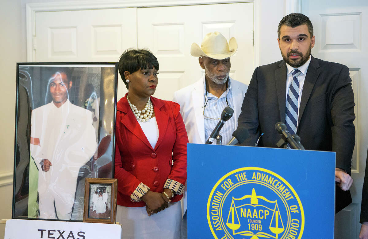 A photo of Danarian Hawkins is seen as his mother, Jacqueline Smith, Dr. James Douglas, and Amin Alehashem, address the media during a news conference, Wednesday, July 29, 2015, in Houston. The Texas Civil Rights Project-Houston announced legal action against the Harris County Sheriff's Office after Hawkins committed suicide while incarcerated at a Harris County jail.
