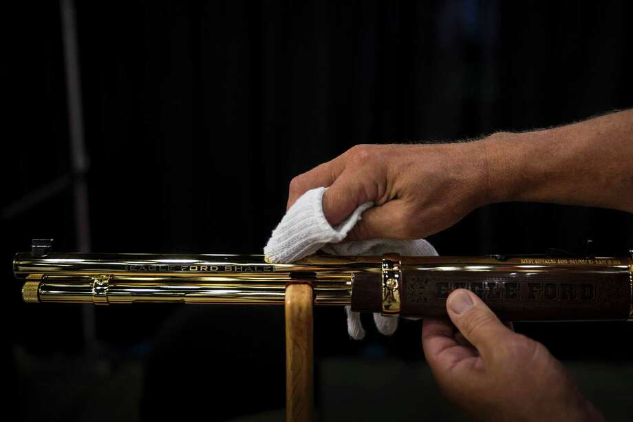 Jack Haines of A&A Engraving, Inc. in Rapid City, South Dakota, cleans a custom-engraved gun Wednesday at his booth at the South Texas Oil Field Expo in San Antonio. Photo: Ray Whitehouse /San Antonio Express-News / 2015 San Antonio Express-News