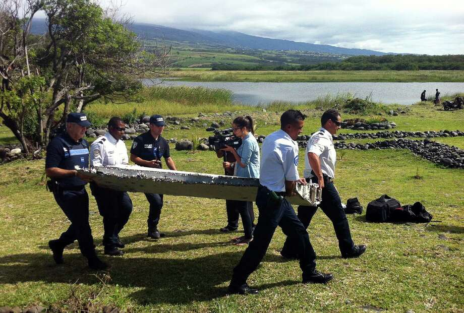 Police recover debris Wednesday that appears to be a piece of a wing from an unidentified aircraft found on the French island of Reunion in the Indian Ocean. Photo: YANNICK PITOU, Stringer / AFP