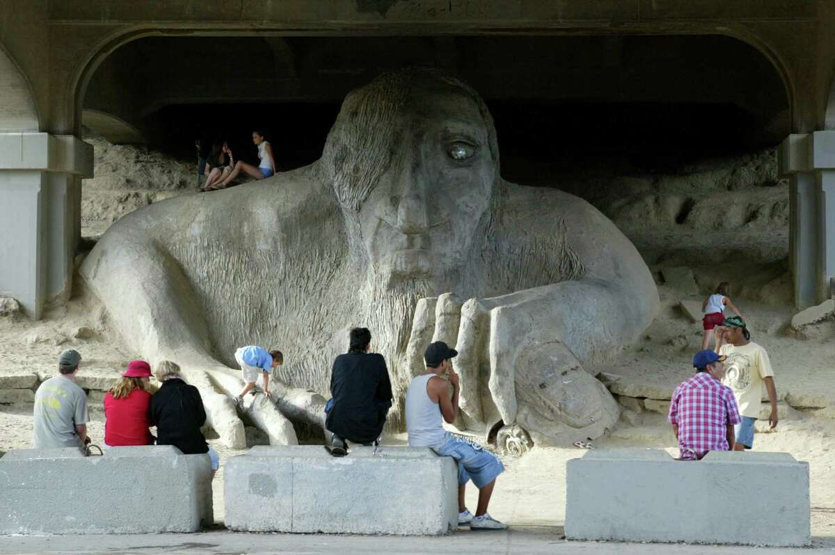 Visitors check out the Fremont Troll under the Aurora Bridge in Fremont. The troll is a favorite spot for visitors, who like to climb on his head. He doesn't mind.
