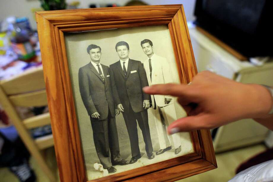 Carla Anaya points to a picture taken in 1959 of her father, Guillermo Manzanares, with his brothers Gustavo (left) and Fabian Manzanares, in Guillermo's Mission District apartment on July 26, 2015. Photo: Michael Short / Michael Short / Special To The Chronicle / ONLINE_YES