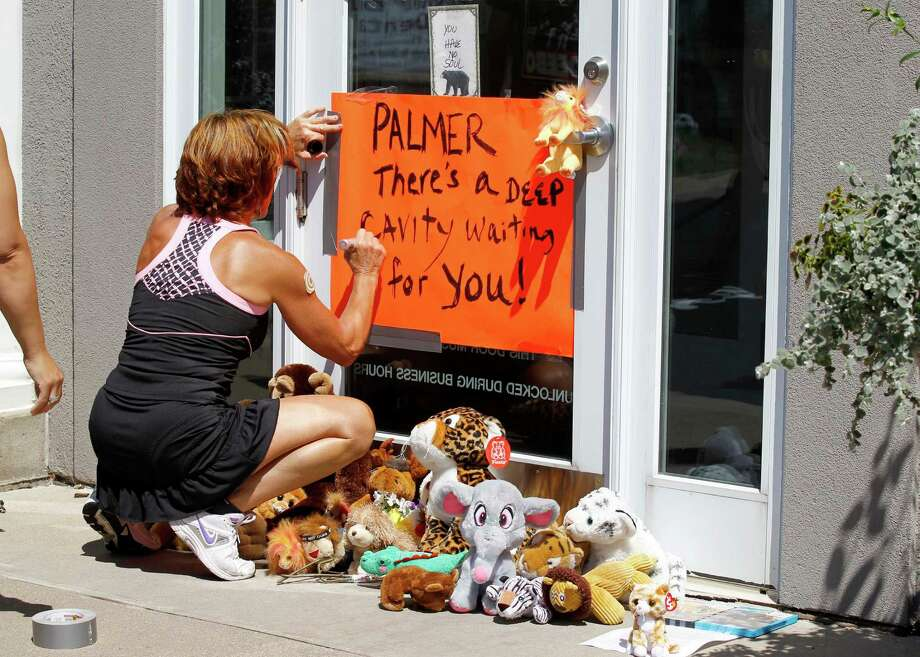 A woman writes on a sign outside Dr. Walter James Palmer's dental office in Bloomington, Minn., Wednesday, July 29, 2015. Palmer reportedly paid $50,000 to track and kill a black-maned lion, just outside Hwange National Park in Zimbabwe. (AP Photo/Ann Heisenfelt) ORG XMIT: MNAH106 Photo: Ann Heisenfelt / FR13069 AP