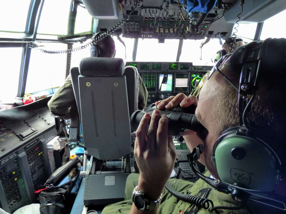 Petty Officer 1st Class Mike Crosby (right) scans the surface of the Atlantic   Ocean while in the cockpit of a Coast Guard rescue helicopter. Photo: Senior CPO Sarah Foster / U.S. Coast Guard / U.S. Coast Guard