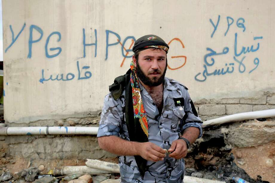 FILE - In this Thursday Jan. 29, 2015 file photo, a Syrian fighter from the Syria-based People's Protection Units better known as the YPG stands in front of a wall covered with graffiti in the town of Sinjar northern Iraq. Turkish jets struck camps belonging to Kurdish militants in northern Iraq Friday and Saturday in what were the first strikes since a peace deal was announced in 2013. The strikes in Iraq targeted the Kurdistan Workers' Party, or PKK, whose affiliates have been effective in battling the Islamic State group. (AP Photo/Bram Janssen, File) ORG XMIT: CAIBS101 Photo: Bram Janssen / AP