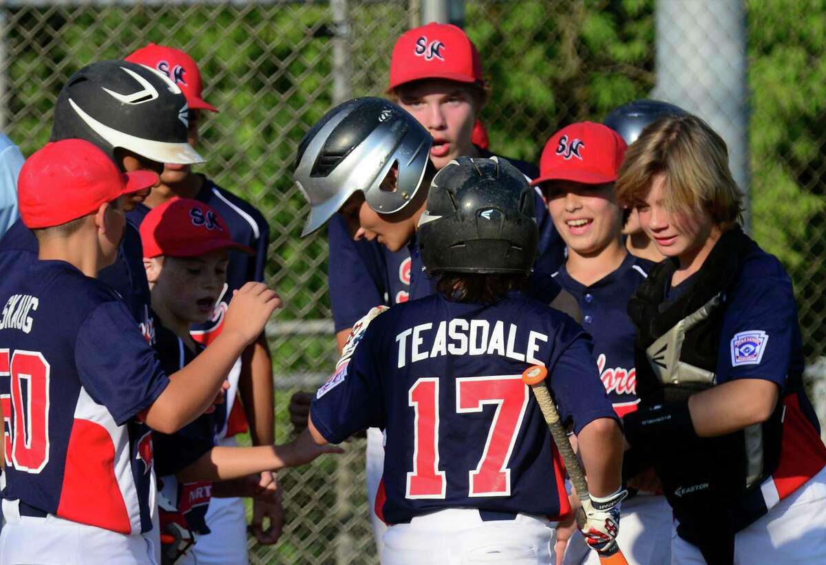 Stamford North contratulates Dave Collazo, center, at home plate after a two-run homer, during Wednesday's Little League game.