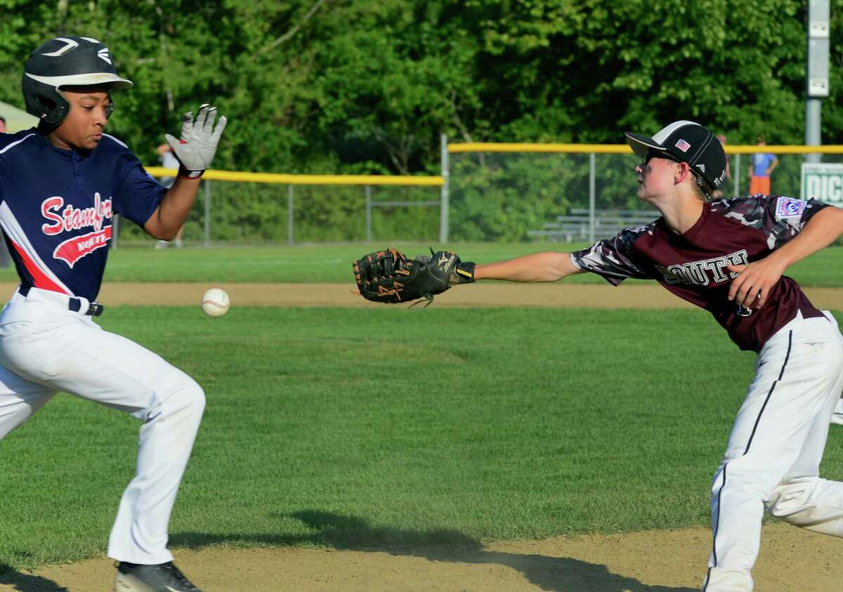 Stamford North's Jaden Dawkins heads to first as Southington's Michael Gurzenda misses the throw during the first game of Little League Championship action in Newington, Conn., on Wednesday July 29, 2015.