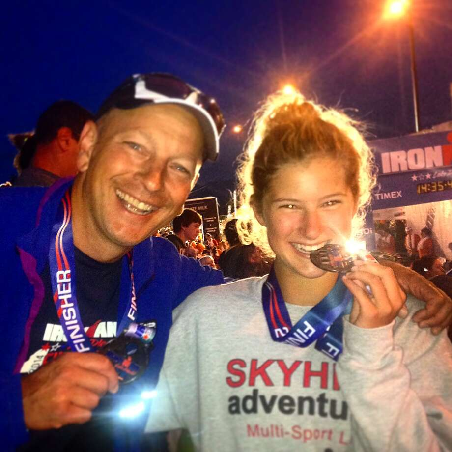 Julia Slyer with her father and fellow Ironman competitor, John Slyer, at her first Ironman Lake Placid in 2014. Julia Slyer won the 18-24 age division in Lake Placid this year, and has qualified for the world championship on Oct. 10, 2015. (Courtesy of the Slyer family)