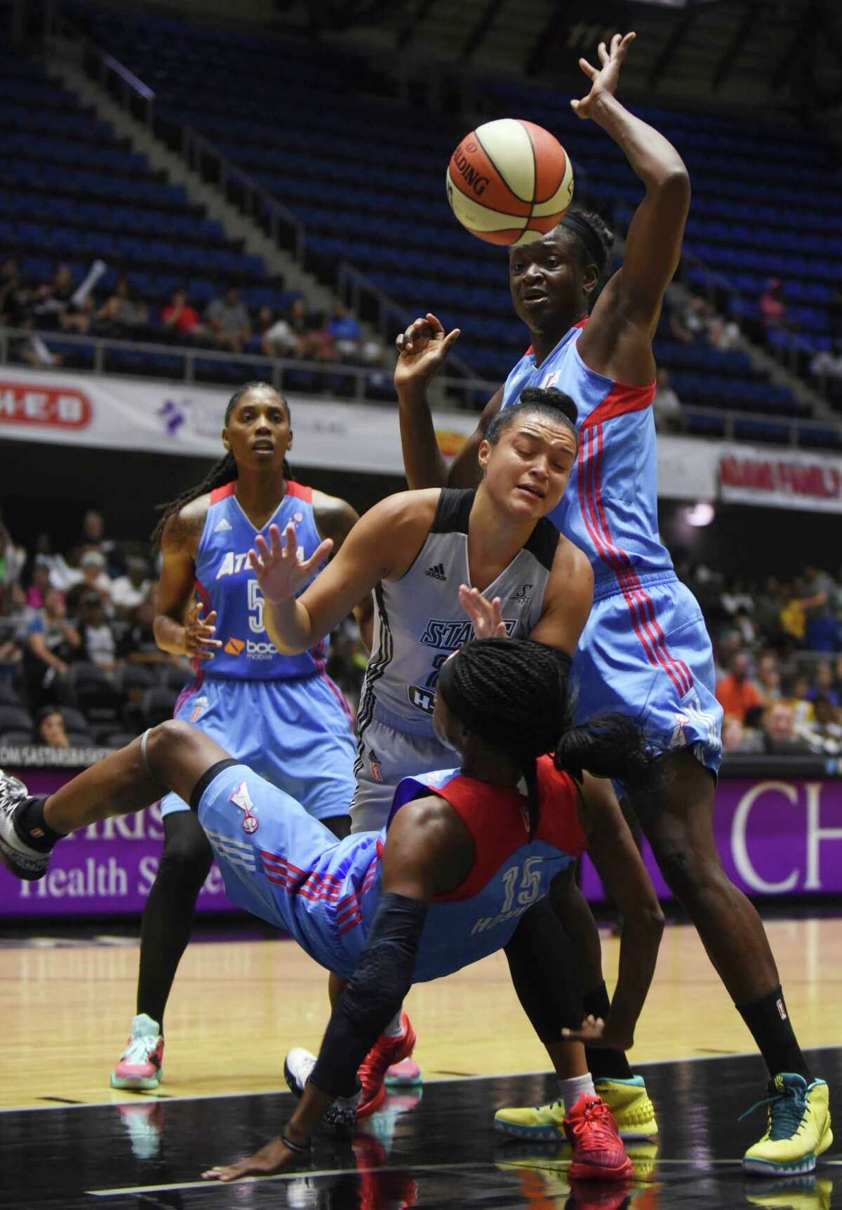 Kayla McBride of the San Antonio Stars, middle, battles during Aneika Henry, top, and Tiffany Hayes of the Atlanta Dream for a loose ball during WNBA action at Freeman Coliseum on Wednesday, July 29, 2015.