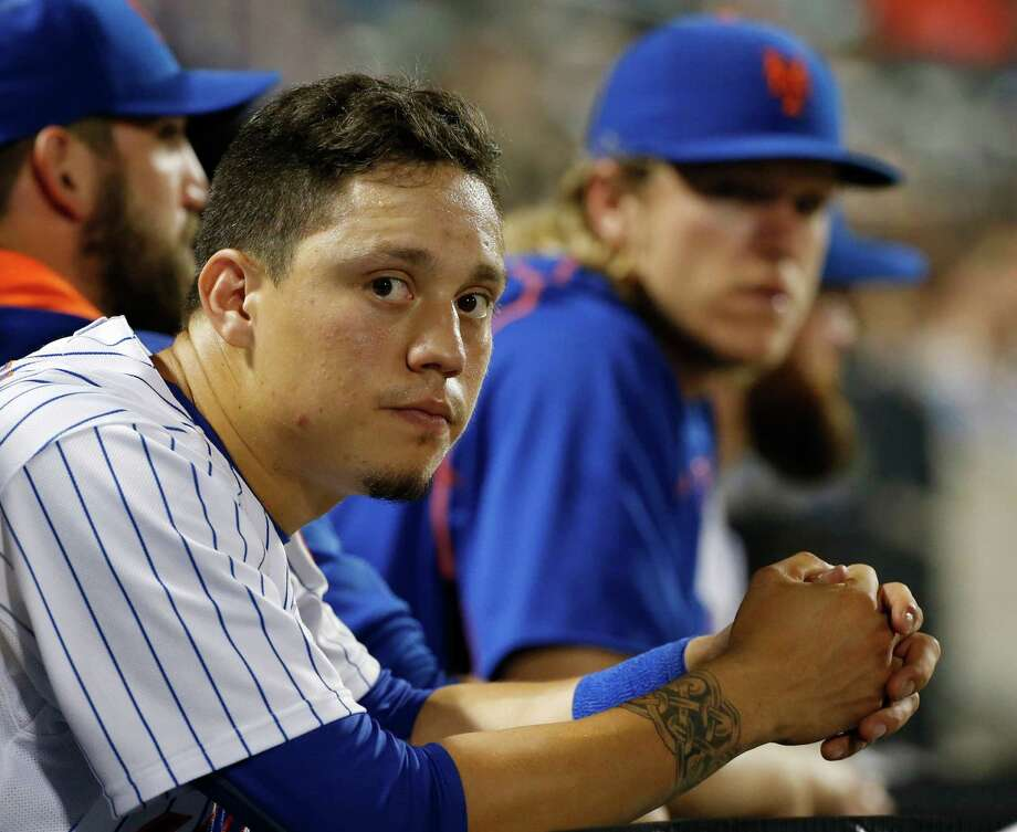 New York Mets' Wilmer Flores, foreground, sits in the dugout during a baseball game against the San Diego Padres in New York, Wednesday, July 29, 2015. (AP Photo/Kathy Willens) ORG XMIT: NYM112 Photo: Kathy Willens / AP