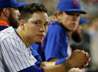 New York Mets' Wilmer Flores, foreground, sits in the dugout during a baseball game against the San Diego Padres in New York, Wednesday, July 29, 2015. (AP Photo/Kathy Willens) ORG XMIT: NYM112