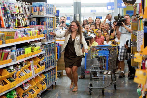"""Cunningham Elementary Principal Anna White shops after she and Westbury High School Band Director, Reginald Washington, not pictured, were granted a charitable shopping spree at Walmart's brand new Galleria Supercenter, Wednesday, July 29, 2015, in Houston. The two were given 82.5 seconds to fill the cart with as much school supplies as possible and were given those supplies to take back to their schools. """"Oh my gosh, it's so exciting for the kids,"""" White said."""