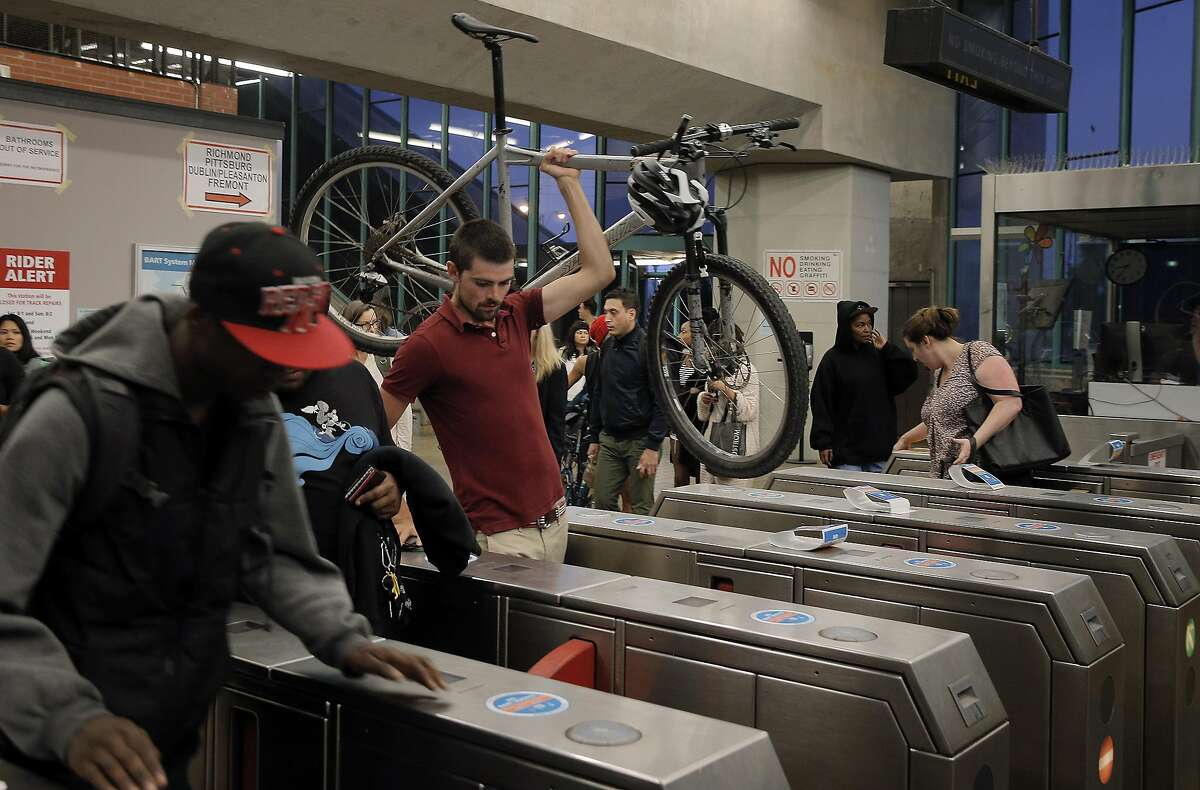 Charles Van Der Loo carries his bike from West Oakland BART station in Oakland, Calif., on Wednesday, July 29, 2015. BART shuts down the Transbay Tube for work on the West Oakland approach to the tube over the weekend of August 1st and 2nd.