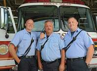 Captain David Stevens, center, stands in front of the rescue squad truck with his sons David Jr., left, and Sean at the Troy Fire Department central fire station on Wednesday, July 29, 2015 in Troy, N.Y. Stevens is retiring after more than 30 years with Troy Fire Department assigned to the rescue squad. His sons also work at the fire station. (Lori Van Buren / Times Union)