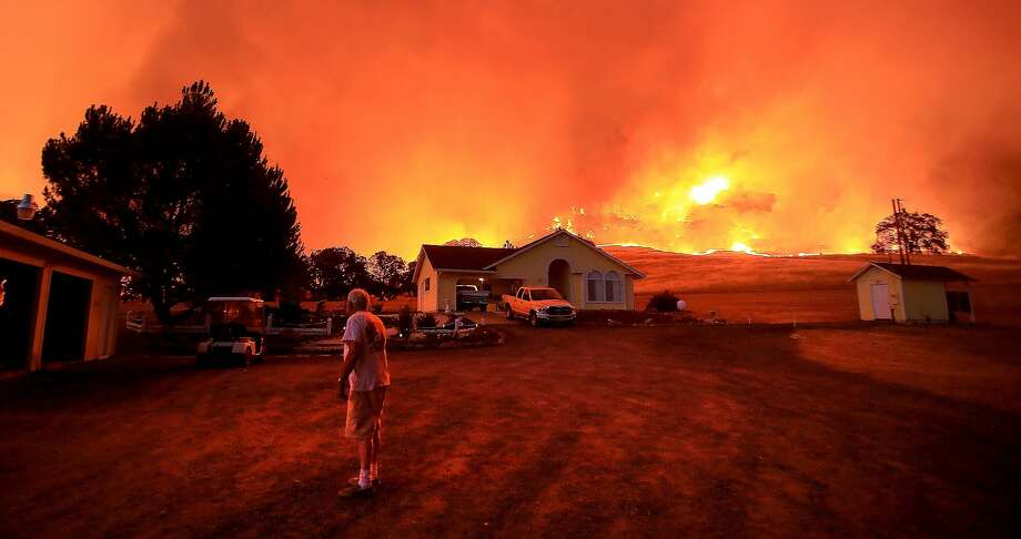 A wall of flames lurches over a ridge as a resident of Morgan Valley Road near Lower Lake, Calif., prepares to evacuate because of the Rock Fire, Wednesday evening July 29, 2015. Photo: Kent Porter, Press Democrat Via AP