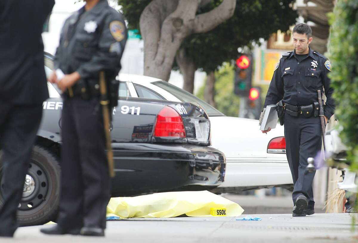 A police officer walks past the body of a man who died in police custody after a hit and run accident and a fight two police officers in San Francisco on Thursday, July 30, 2015. Calif.