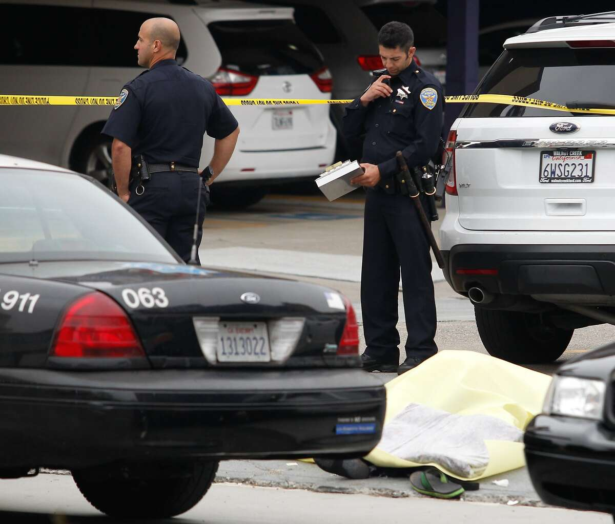 A police officers investigate near the body of a man who died in police custody after a hit and run accident and a fight two police officers in San Francisco on Thursday, July 30, 2015. Calif.