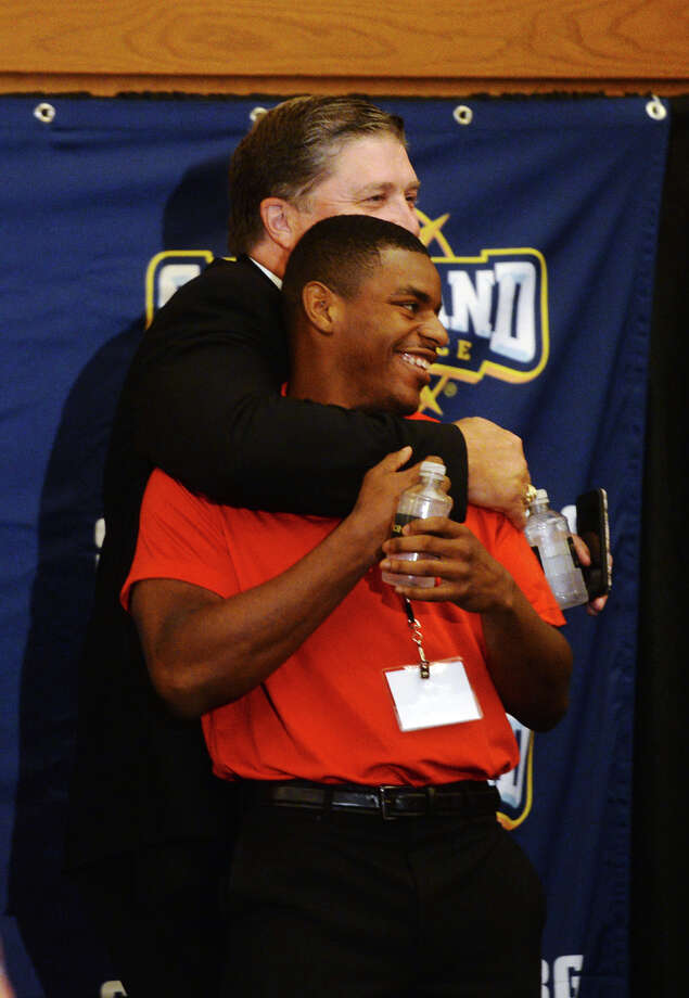 Lamar's Xavier Bethany gets a hug from Coach Ray Woodard after the Cardinals' turn at the Southland Conference media day dais Wednesday afternoon. The Southland Conference held their annual football media day at the L'Auberge Resort in Lake Charles on Wednesday. Lamar University was represented by Coach Ray Woodard, wide receiver Reggie Begelton, and defensive back Xavier Bethany.  Photo taken Wednesday 7/29/15  Jake Daniels/The Enterprise Photo: Jake Daniels / ©2015 The Beaumont Enterprise/Jake Daniels