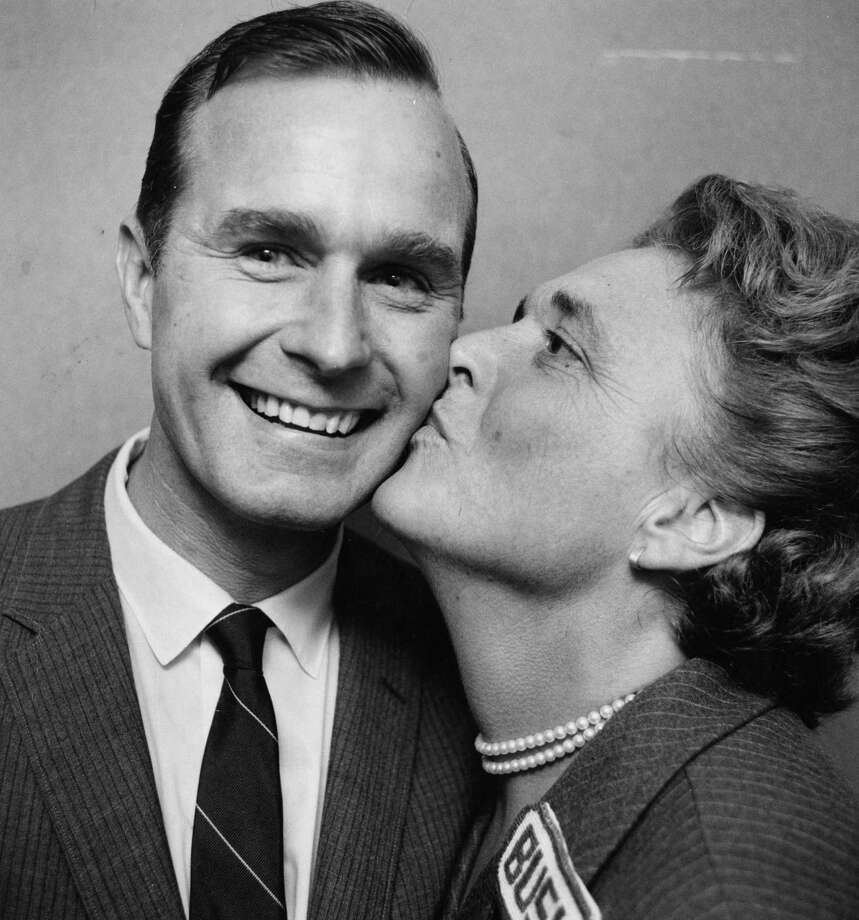 Newly-elected U.S. Rep. George Bush flashes a winner's smile as his wife, Barbara, gives him a victory kiss following his 1966 election to a seat in from the 7th district in Texas.