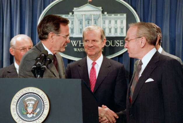 President George H.W. Bush turns and shakes hand with House Speaker Jim Wright of Texas after he announced in the White House briefing room in Washington, on Friday, March 24, 1989 that he is unveiling a Bipartisan Contra aid plan as the first plank of his emerging foreign policy.   Center is Secretary of State James Baker and left is House Minority Leader Robert Michel of Ill. Photo: Barry Thumma, ASSOCIATED PRESS / AP