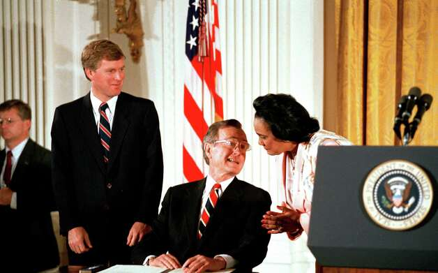 Coretta Scott King has a word with President Bush before he signed legislation at the White House, May 17, 1989, extending the Martin Luther King, Jr. Federal Holiday Commission.  Vice President Dan Quayle stands at left. Photo: BARRY THUMMA, ASSOCIATED PRESS / AP