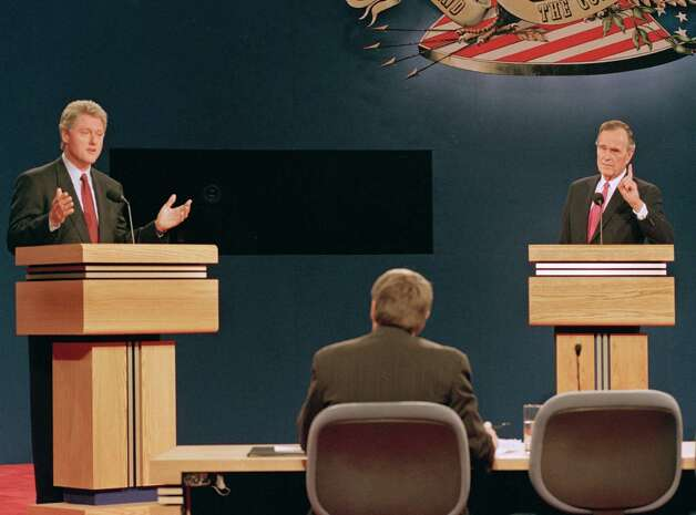 Democratic presidential nominee Gov. Bill Clinton, left, answers a question during Monday night's presidential debate as U.S. President George Bush tries to make a point at Michigan State University in East Lansing, Mich., Oct. 19, 1992. Photo: RON EDMONDS, ASSOCIATED PRESS / AP