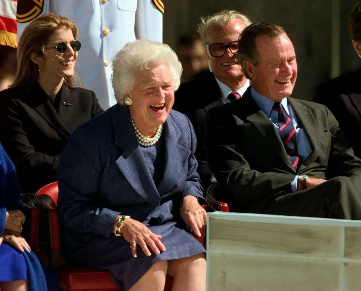 Former First Lady Barbara Bush and former President George Bush laugh at former President Jimmy Carter's speech during the dedication of the George Bush Presidential Library in College Station, Texas, Thursday, Nov. 6, 1997.