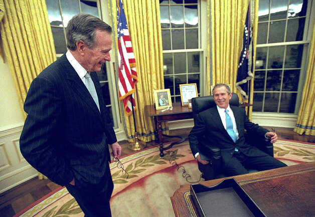 President George W. Bush talks to his father, former President Bush as he sits at his desk in the Oval Office in this file photo for the first time on Inaugural Day, Jan. 20, 2001. In many ways, large and small, George W. Bush's presidency has become a mirror image of his fathers. Photo: ERIC DRAPER, AP / WHITE HOUSE