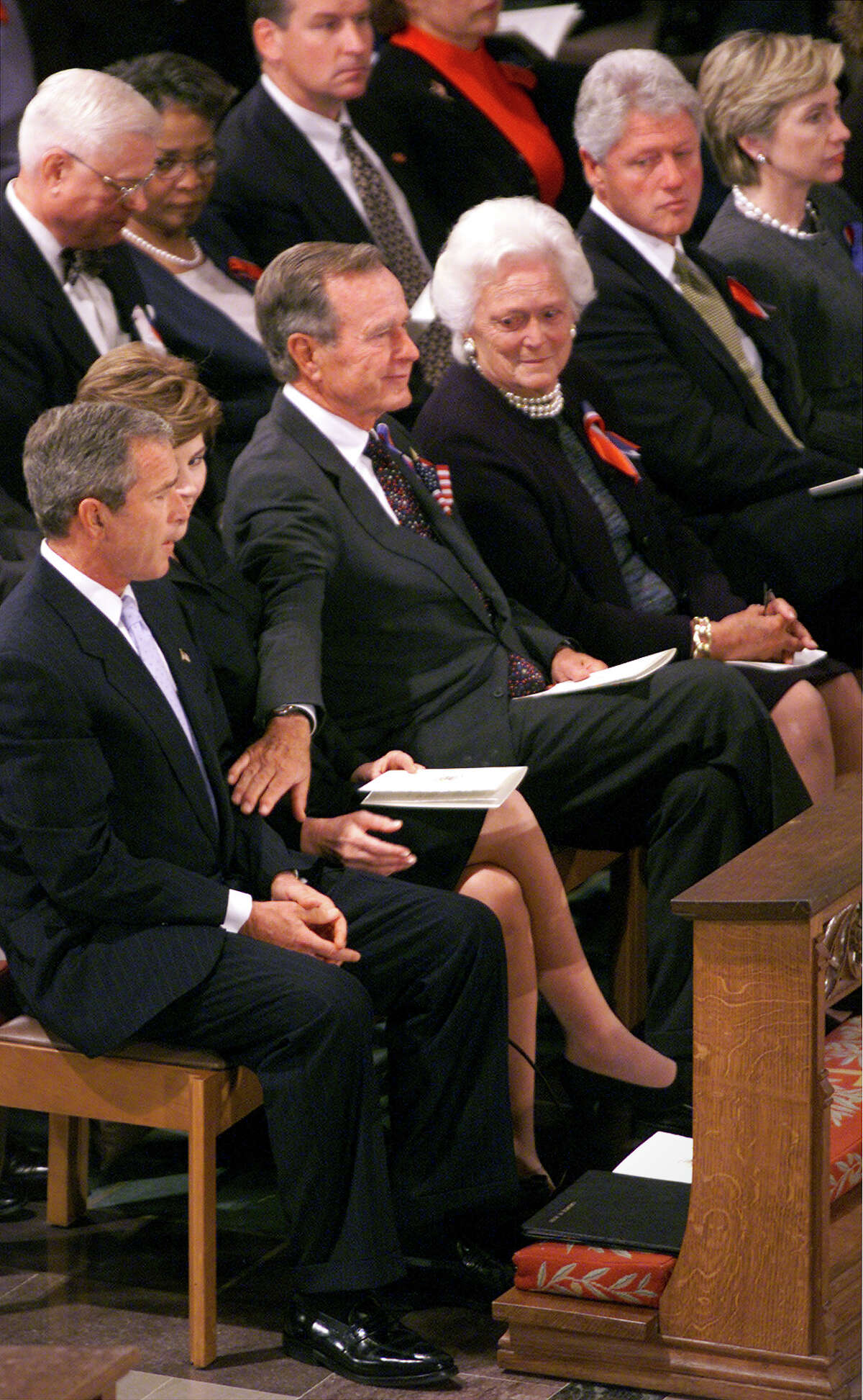 President George W. Bush, left, receives a comforting pat on the arm from his father, former President George H.W. Bush, after speaking at a prayer service remembering the victims of Tuesday's terrorist attacks on Friday, September 14, 2001.