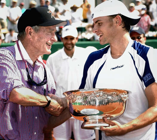 Former President Bush, left, presents the winner's trophy to Andy Roddick, right, after Roddick defeated Pete Sampras, rear center, in the finals of the U.S. Clay Court Championships in Houston, Sunday, April 28, 2002. Photo: DAVID J. PHILLIP, AP / AP
