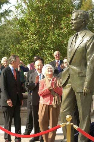 President George H.W. and Barbara Bush along with Houston Mayor Bill White (behind Barbara Bush) and event co-chair Charles Foster (foreground left, back to camera) were at the unveiling of a statue and plaza honoring the former president, 12/02/2004 in Sesquicentennial Park. Photo: Steve Ueckert, © Houston Chronicle / Houston Chronicle