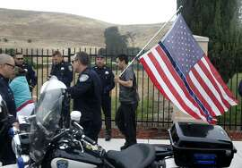 Rafael Cerna carries a flag decorated with a blue stripe past police officers waiting for the funeral procession for Hayward police Sgt. Scott Lunger to depart Chapel of the Chimes mortuary in Hayward, Calif. on Thursday, July 30, 2015.
