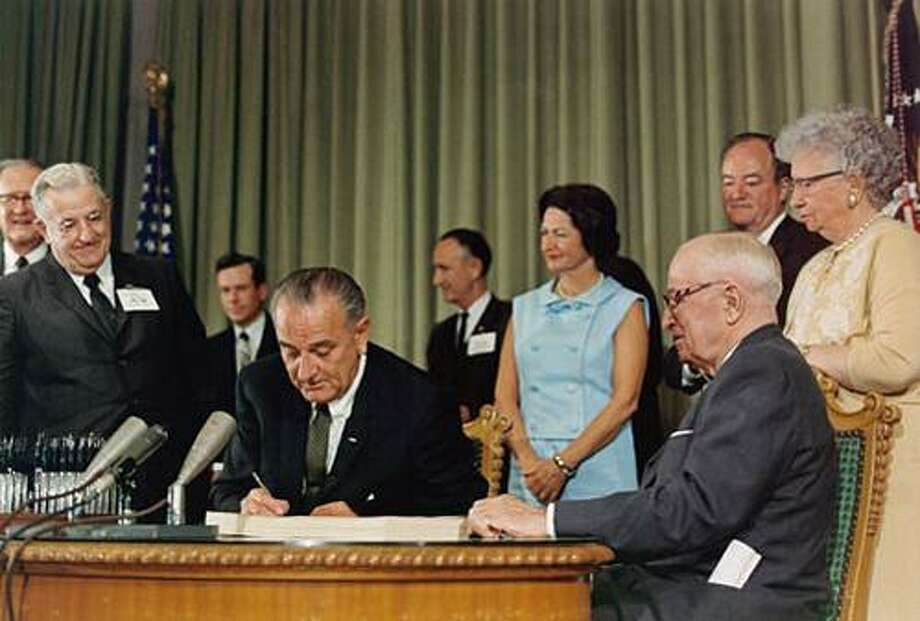 President Johnson signing the Medicare program into law, July 30, 1965. Shown with the President (on the right in the photo) are (left to right) Mrs. Johnson; former President Harry Truman; Vice-President Hubert Humphrey; and Mrs. Truman. Photo courtesy of LBJ Presidential Library.