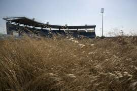 In this photo taken on Thursday, July 16, 2015, an abandoned stadium used for baseball events during Athens' 2004 Olympic games is seen through weeds at the old airport of Athens. Now, in a bid to get a third European bailout, the ruling party has done an about face and is pledging to fast-track the waterfront project plus a host of other privatization efforts aimed at generating cash to help to reduce Greece's 320 billion euros national debt.(AP Photo/Petros Giannakouris)