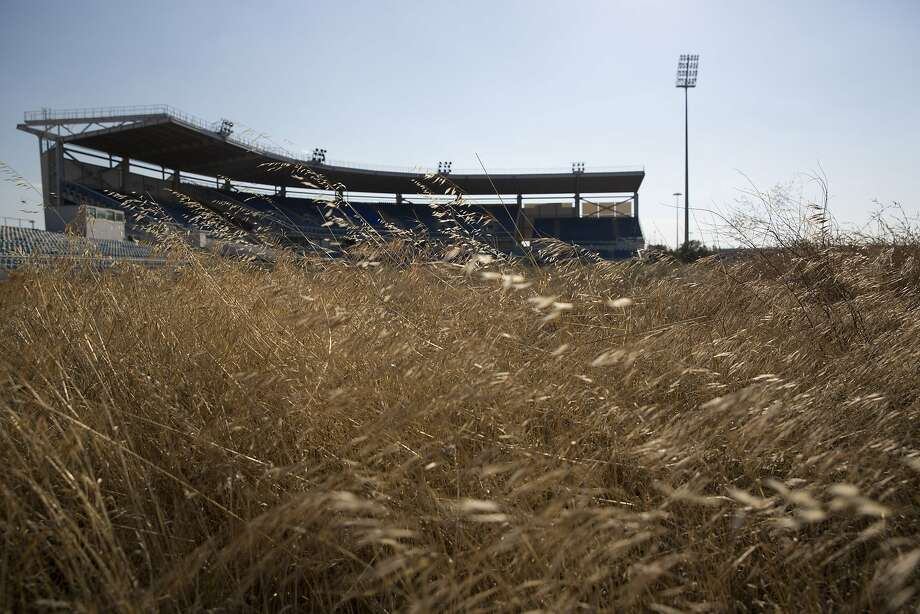 In this photo taken on Thursday, July 16, 2015, an abandoned stadium used for baseball events during Athens' 2004 Olympic games is seen through weeds at the old airport of Athens. Now, in a bid to get a third European bailout, the ruling party has done an about face and is pledging to fast-track the waterfront project plus a host of other privatization efforts aimed at generating cash to help to reduce Greece's 320 billion euros national debt.(AP Photo/Petros Giannakouris) Photo: Petros Giannakouris, Associated Press
