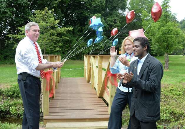 Schenectady Mayor Gary McCarthy, Schenectady High School Principal Diane Wilkinson and student Ahmed Ahmad cut a ribbon opening the bridge that students of the 21st Century Summer Learning Program designed and constructed on the 18th hole of the Disc Golf Course in Central Park Thursday July 30, 2015 in Schenectady, NY. (John Carl D'Annibale / Times Union) Photo: John Carl D'Annibale / 10032812A