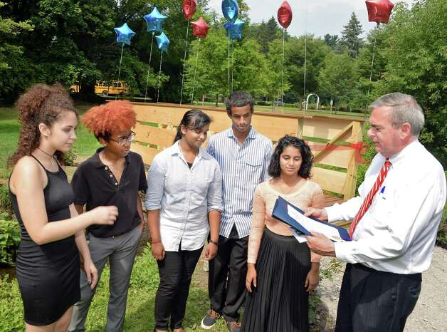 Schenectady High School students, from left, Mikayla Foster, Christopher Colon, Sara Ali, Maazin Ahmed and Cindy Ganesh are shown a proclamation by Schenectady Mayor Gary McCarthy before ceremonies unveiling the bridge that students of the 21st Century Summer Learning Program designed and constructed on the 18th hole of the Disc Golf Course in Central Park Thursday July 30, 2015 in Schenectady, NY. (John Carl D'Annibale / Times Union) Photo: John Carl D'Annibale / 10032812A