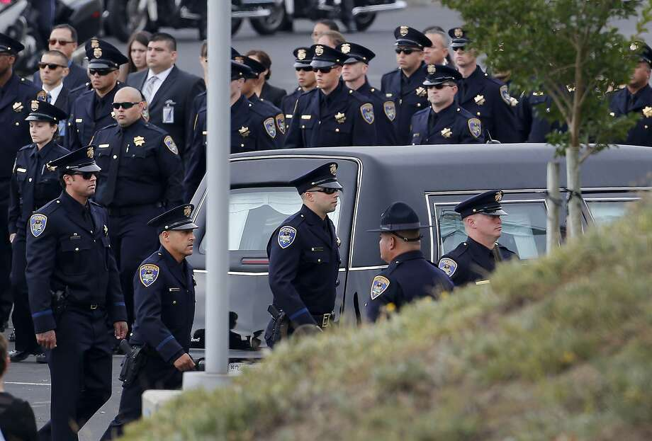 Hayward police officers passed by the hearse that carried their fallen Sergeant. Thousands attended the funeral for slain Hayward, Calif. police Sgt. Scott Lunger at the Oracle Arena in Oakland Thursday July 30, 2015. Photo: Brant Ward, The Chronicle