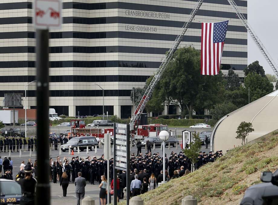 The hearse containing the remains of Sgt. Scott Lunger arrived at the southern parking lot at Oracle Arena.  In the foreground are Hayward police officers. Thousands attended the funeral for slain Hayward, Calif. police Sgt. Scott Lunger at the Oracle Arena in Oakland Thursday July 30, 2015. Photo: Brant Ward, The Chronicle