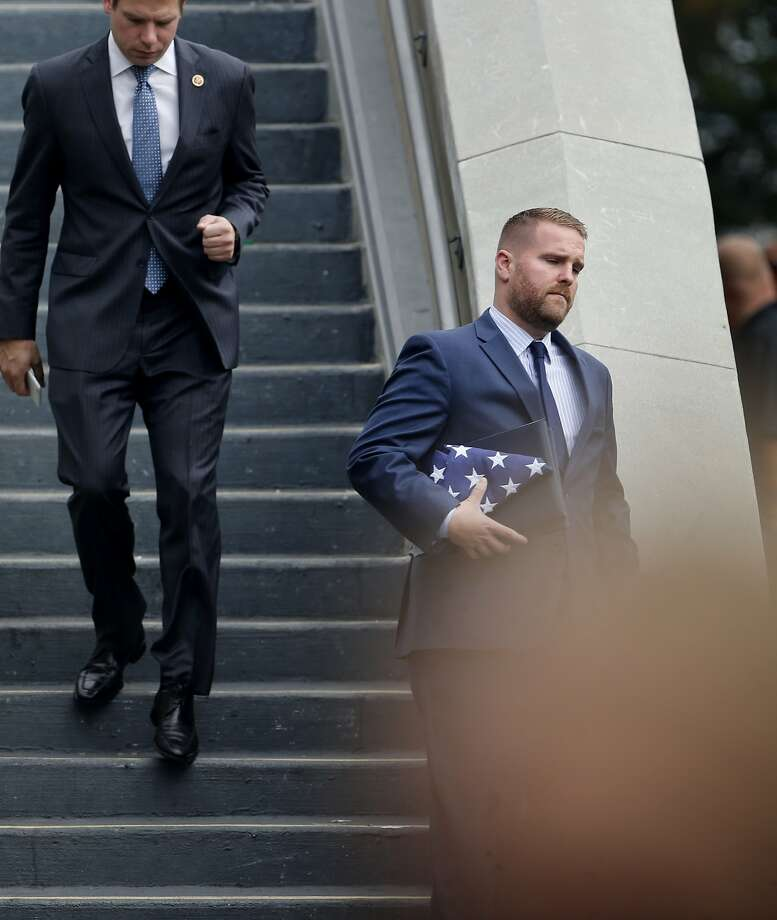 An unidentified man carrying a folded American flag descends a staircase at Oracle. Thousands attended the funeral for slain Hayward, Calif. police Sgt. Scott Lunger at the Oracle Arena in Oakland Thursday July 30, 2015. Photo: Brant Ward, The Chronicle