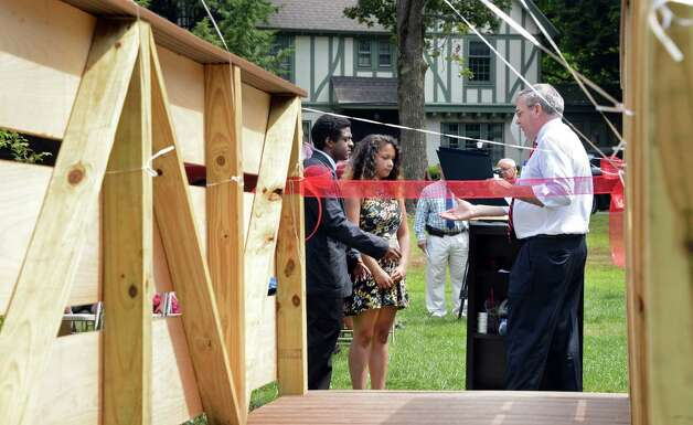 Schenectady Mayor Gary McCarthy presents a proclamation to Schenectady High School students Ahmed Ahmad, left, and Hadiyah Fowler during ceremonies unveiling the bridge that students of the 21st Century Summer Learning Program designed and constructed on the 18th hole of the Disc Golf Course in Central Park Thursday July 30, 2015 in Schenectady, NY. (John Carl D'Annibale / Times Union) Photo: John Carl D'Annibale / 10032812A