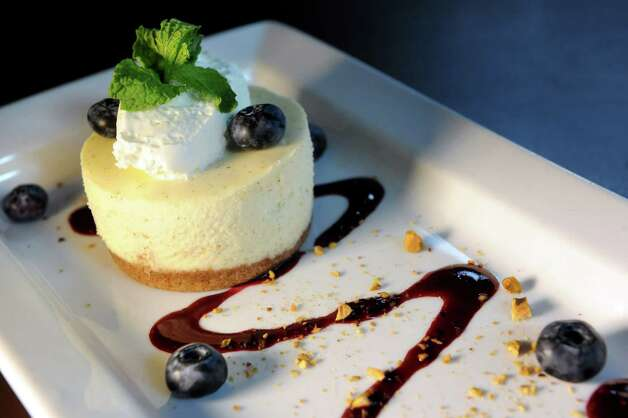 Cheesecake with a graham-cracker crust, local blueberry sauce, creme fraiche and mint sprig on Friday, July 24, 2015, at Max London's in Saratoga Springs, N.Y. (Cindy Schultz / Times Union) Photo: Cindy Schultz / 00032745A
