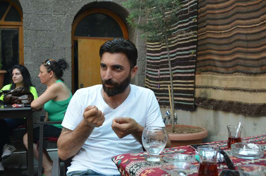 "Musician Axin Bro, 36, talks to the Associated Press at a cafe in Diyarbakir, southeastern Turkey, Thursday, July 30, 2015. ""We are used to this. Kurds have witnessed betrayal for centuries"" says Bro. In Turkey's Kurdish heartland, the government's renewed military onslaught against the rebels has left many people crying treachery — with suspicions rife that Turkey used a brief offensive against IS as a cover to launch a broad attack against the Kurdistan Workers Party, or PKK. Photo: Desmond Butler, Associated Press"
