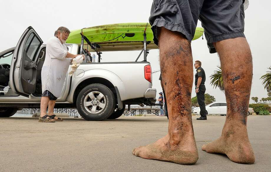 Henry Duncan (left) and Bob Seiler, legs covered in oil, stand in the Goleta Beach parking lot with their oil-covered kayaks, on the truck at rear, in Goleta, Santa Barbara County. Photo: Mike Eliason, Associated Press