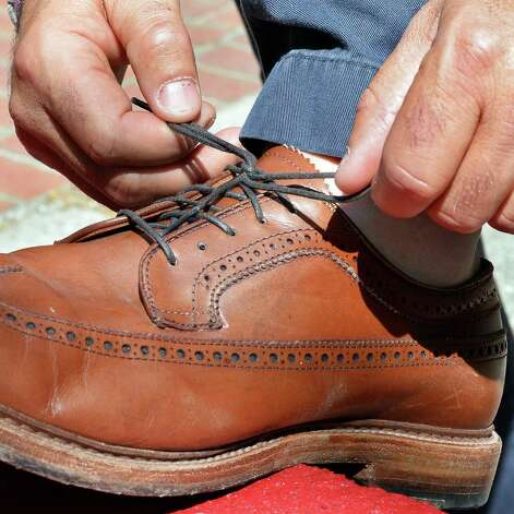 Matt Baumgartner ties an Alden shoe outside his Olde English Pub on Broadway Friday May 29, 2015 in Albany, NY.   (John Carl D'Annibale / Times Union) Photo: John Carl D'Annibale / 00031984C