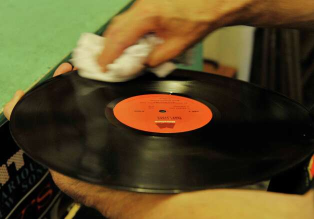 A record is cleaned by an employee before being put back into its sleeve inside the John Doe Records store on Warren St. on Thursday, June 25, 2015, in Hudson, N.Y.  (Paul Buckowski / Times Union) Photo: PAUL BUCKOWSKI / 00032353A