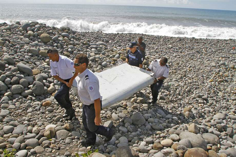 French police officers carry a piece of debris from a plane in Saint-Andre, Reunion Island. Photo: Lucas Marie, Associated Press