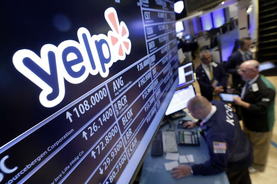 Traders gather at the post that handles Yelp, on the floor of the New York Stock Exchange, Wednesday, July 29, 2015. Yelp plunged 28 percent after sinking to a loss and cutting its outlook. (AP Photo/Richard Drew) Photo: Richard Drew, Associated Press